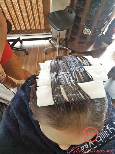 rolls of tissue in between layers of hair during hair straightening treatment at lifestyle salon